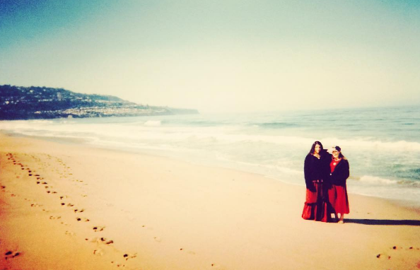 A faded photograph of an almost-empty beach. In the distance are two teenaged girls wearing long red dresses and black jackets. They are too far away to make out their expressions, but they appear to be looking at the camera. They cast a long shadow.