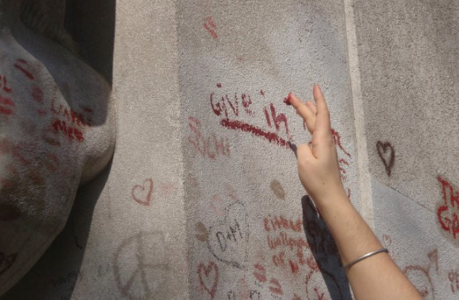 "A photograph of someone graffiti-ing Oscar Wilde's tomb: only an arm is visible, finger-painting the phrase ""GIVE IN"" in lipstick on the side of the tomb."